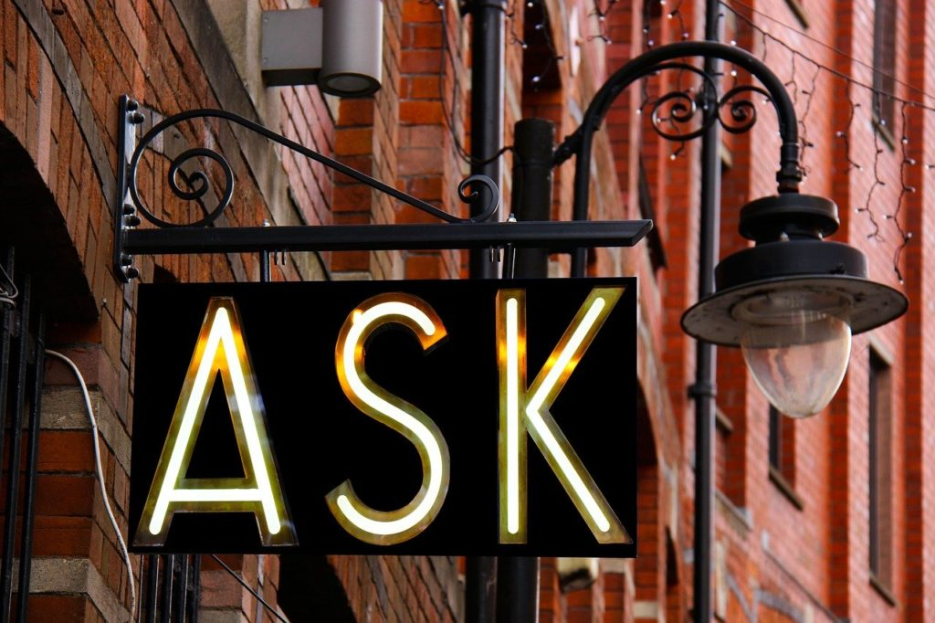 "Storefront sign that says ""ASK"" in front of lamp and red building walls"