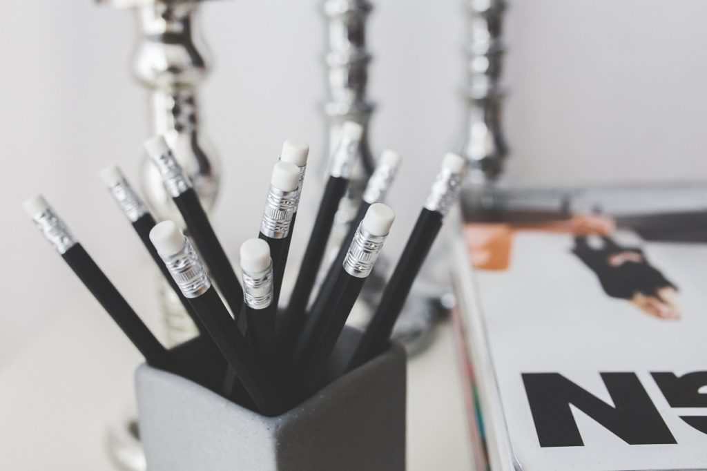 Close up shot of multiple black pencils in a cup with a notebook in the background