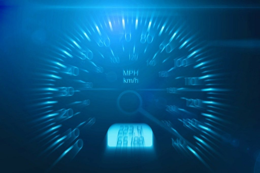 Speedometer closeup (showing blue LED) representing fast speed